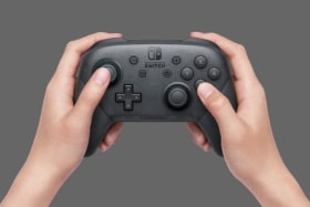 Nintendo Switch Pro Controller in a pair of hands