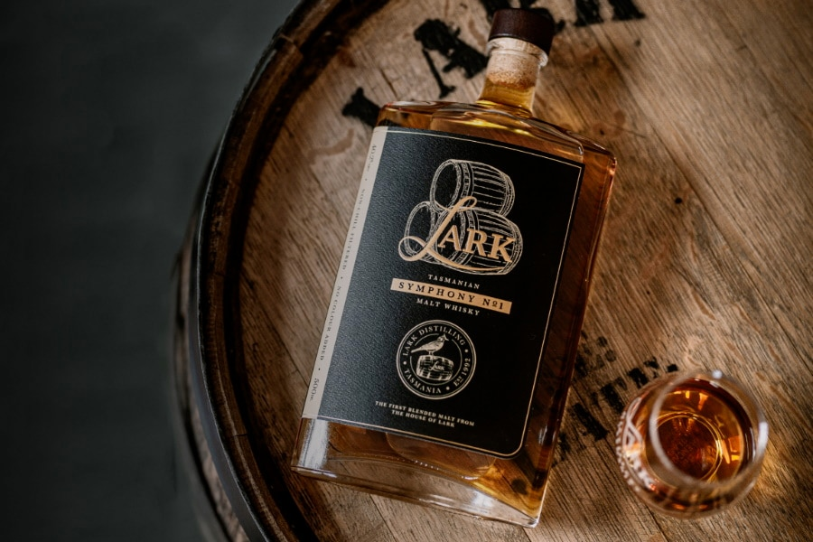 Fallen over bottle of Lark Distilling Co. Symphony No. 1 Whisky on a barrel top next to a glass