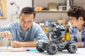 A man using a compass on table as a boy watches him. A DJI Robomaster robot on table