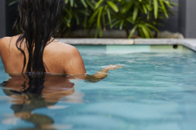 A woman standing in a swimming pool with her back towards camera