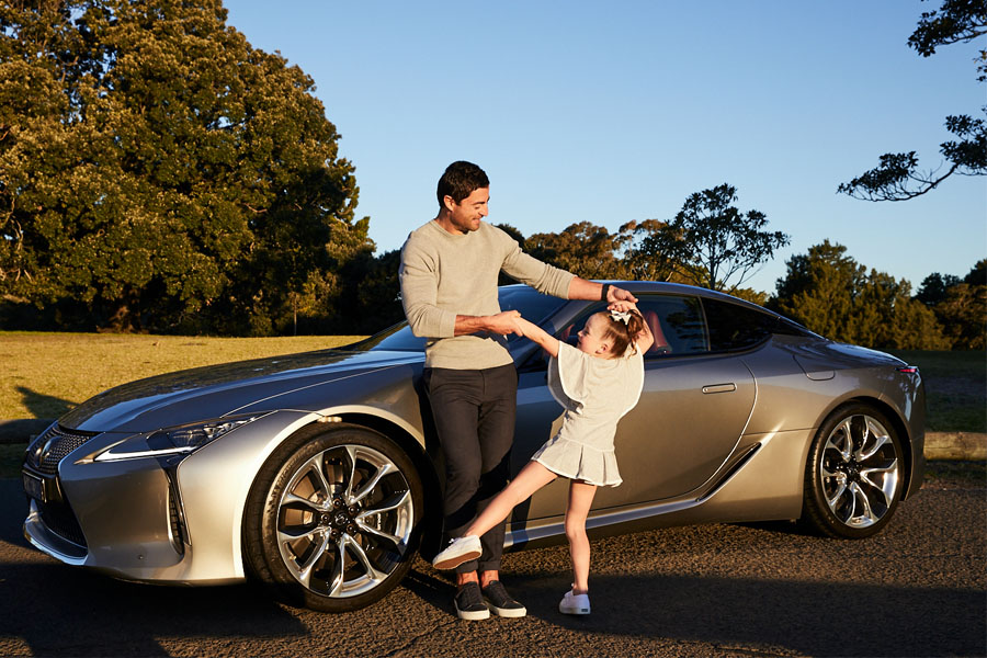 Anthony Minichiello playing with his daughter near his Lexus