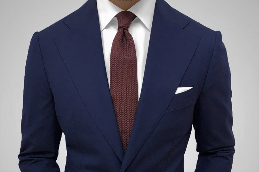A torso of a man in suit with Dark Knot accessories