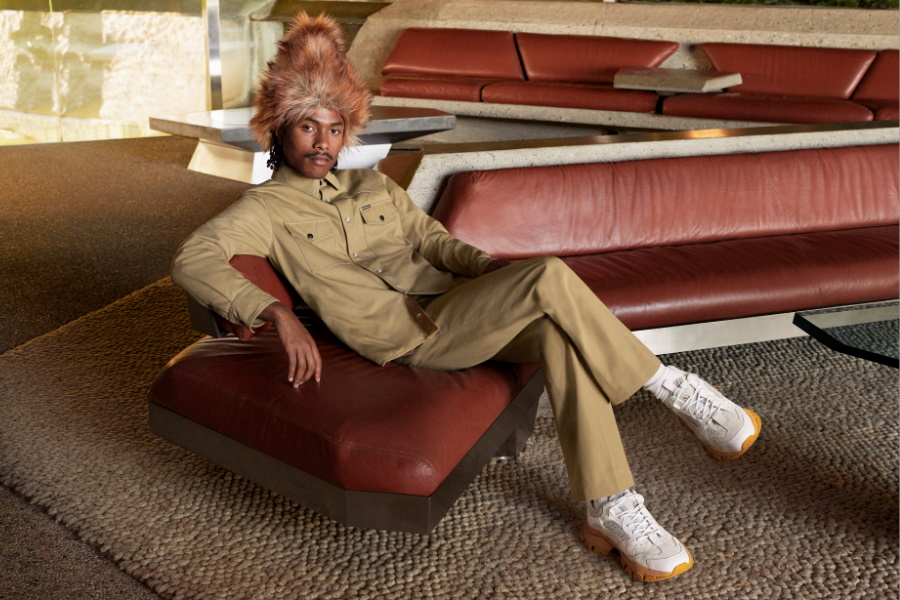 A model sitting on a couch wearingMoncler 1952 Men's Collection khakhi clothes