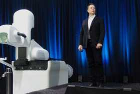 Elon Musk holding a mic in front of a white machine at an event