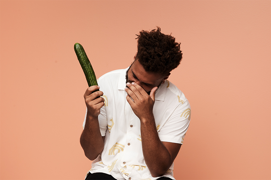 A man holding a huge cucumber in one hand and bringing other closer face as he laughs