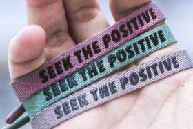 "Three Rastaclat bracelets with ""Seek the positive"" in a palm"