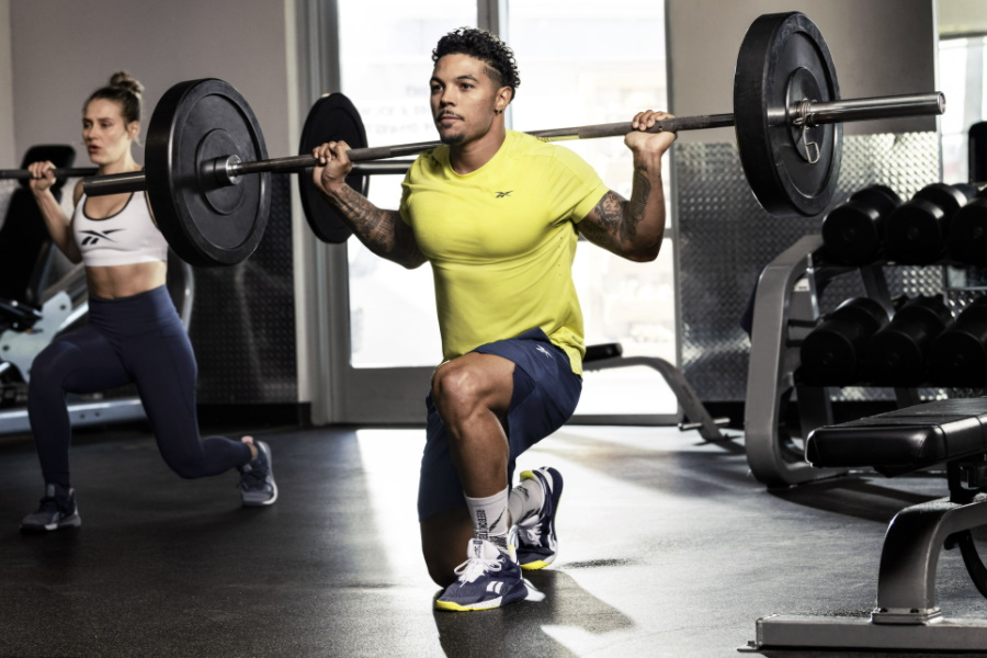 Man lifting barbell on his shoulders sitting on one knee