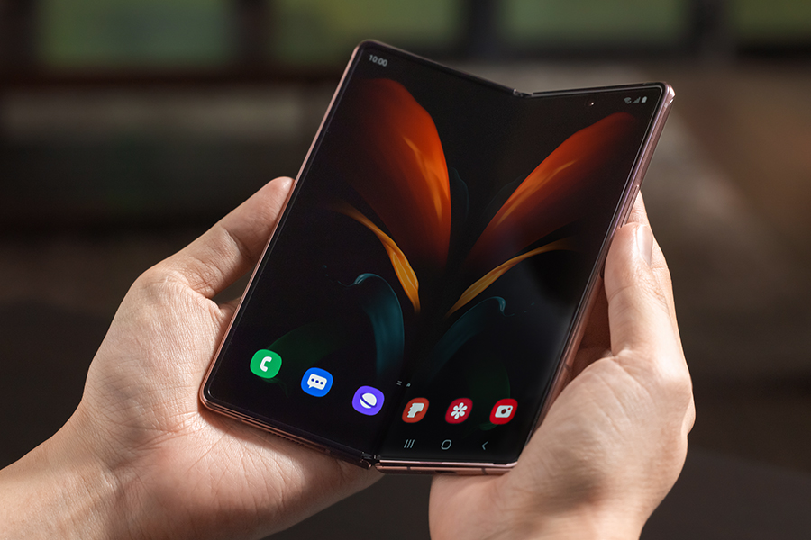 A pair of hands holding an unfolded Samsung Galaxy Fold phone
