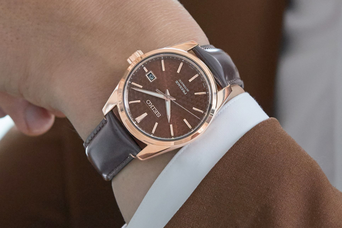 A hand with a Seiko Presage brown dial, brown strap watch