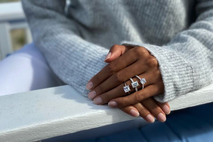 A close up of a hand over another with three diamond rings from Siroo on ring finger