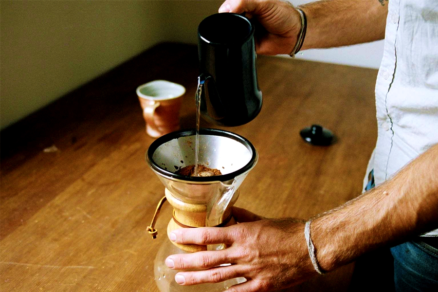 Hand pouring water over coffee strainer placed on a kettle