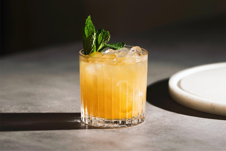 A yellow cocktail in a glass