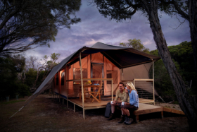 Man and woman sitting on a wooden platform in front of cabin-like elevated tent