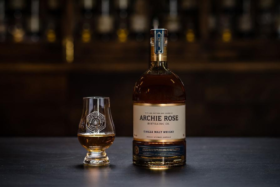 A glass and bottle of of Archie Rose Single Malt whiskey