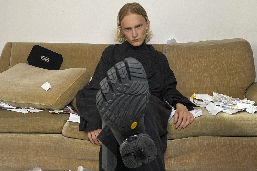 Sole of Balenciaga Toe Sneaker raised to camera in focus with the model wearing it sitting on a sofa in background