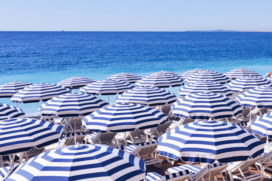 A beach full of umbrellas with chairs under them