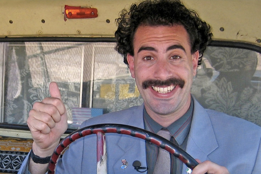 Borat showing a thumbs up with one hand on steering wheel