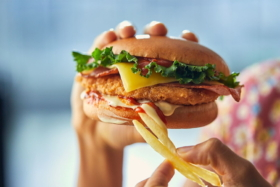 A pair of hands holding fries and McDonald's Chicken Parmi Burger