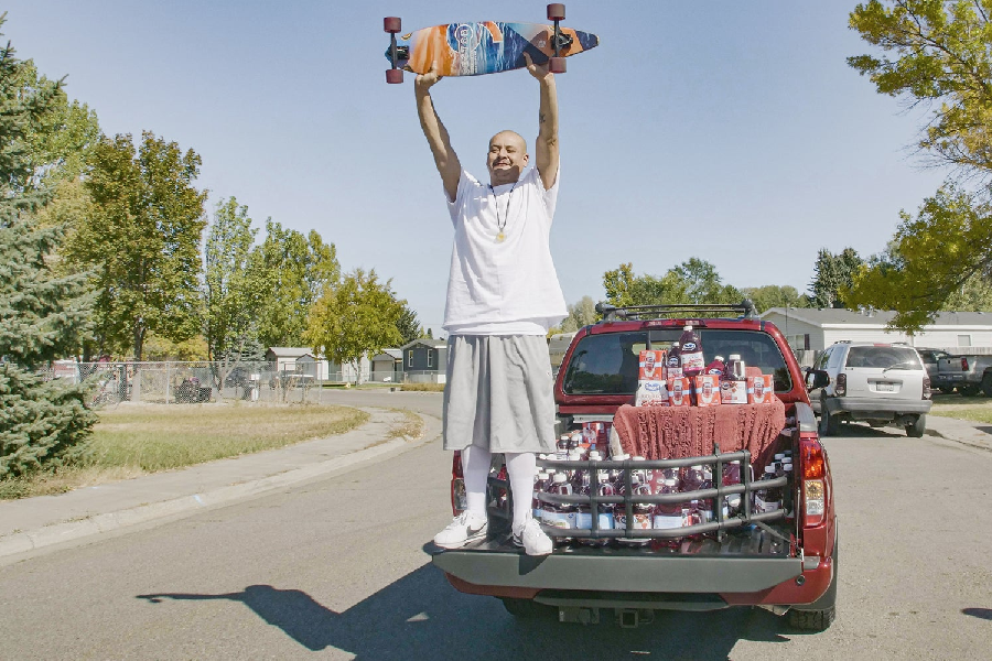 DoggFace holding his skateboard in air with both hands standing in cargo of his truck
