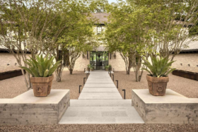 Paved path towards the door of Joe Rogan's Texas Ranch with plants on both sides