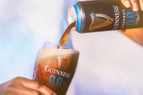 A hand pouringGuinness Non-Alcoholic Pint in a glass out of a can