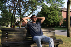 A man wearing Social Citizen t-shirt on a bench with his hands behind his head