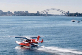 A seaplane in water with Sydney Harbour Bridge in background