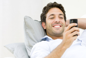 A man in bed smiling looking at his phone