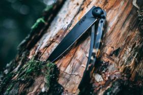 A Deejo knife on a tree trunk