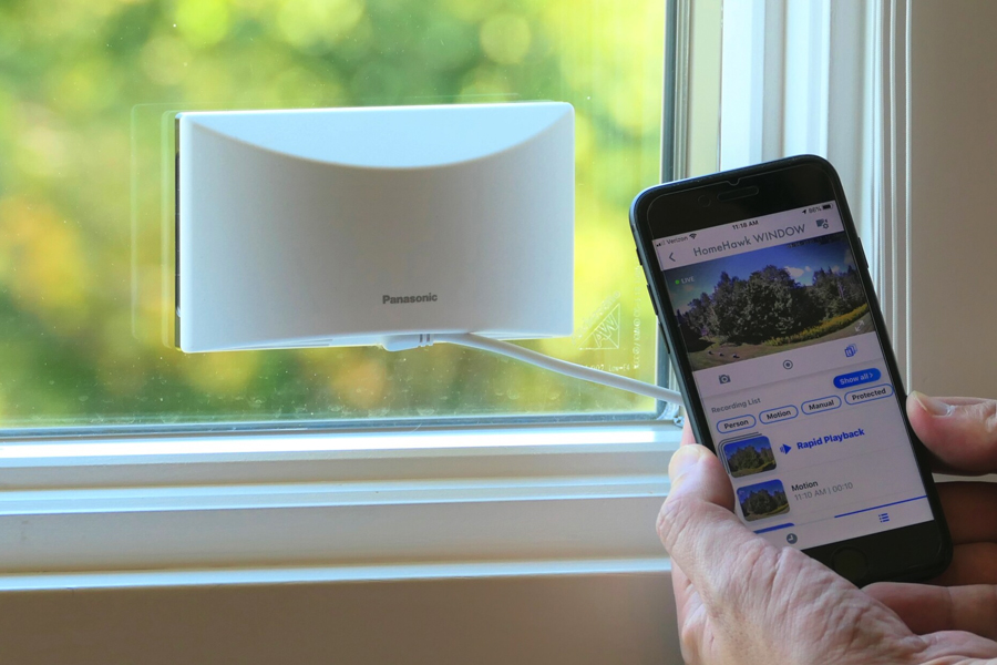 A phone with Panasonic HomeHawk app open on it and Panasonic HomeHawk Window in background
