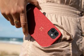 A hand puttingan iPhone 12 with MAISON de SABRE case in trouser pocket