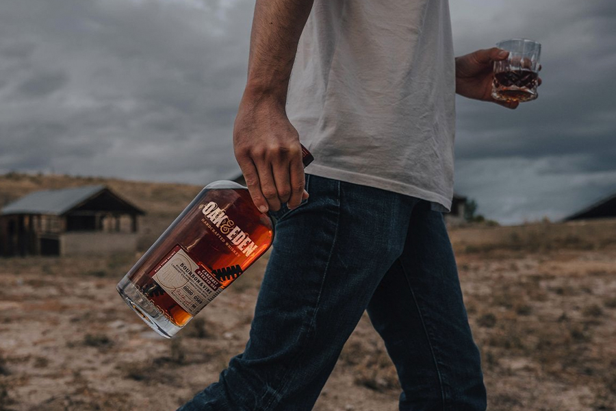 Oak & Eden Whiskey in hand of a man holding a glass of whiskey in the other