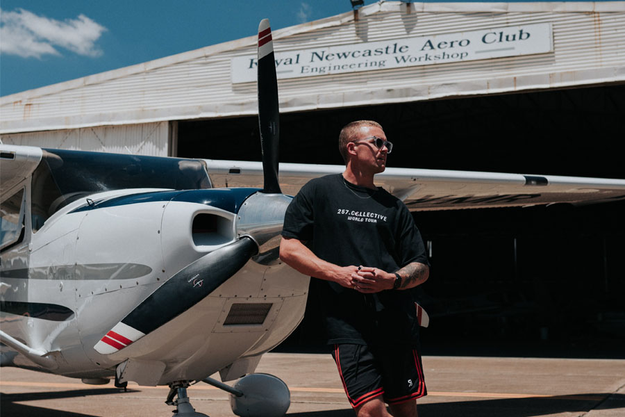 A man in a 257 Collective t-shirt standing leaning on a small plane's front propeller