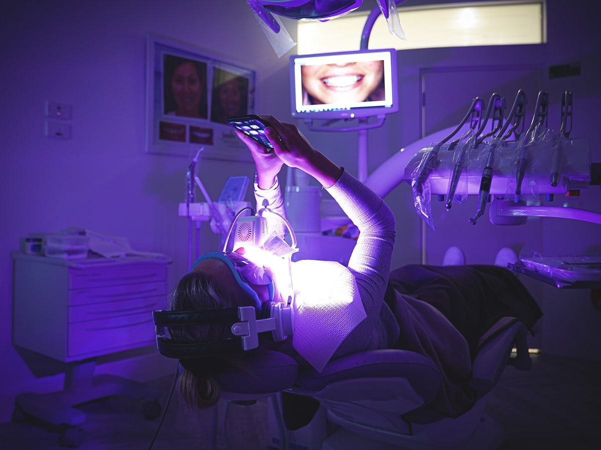 woman on a dentist's chair getting teeth whitening treatment at cosmetic laser dentistry centre