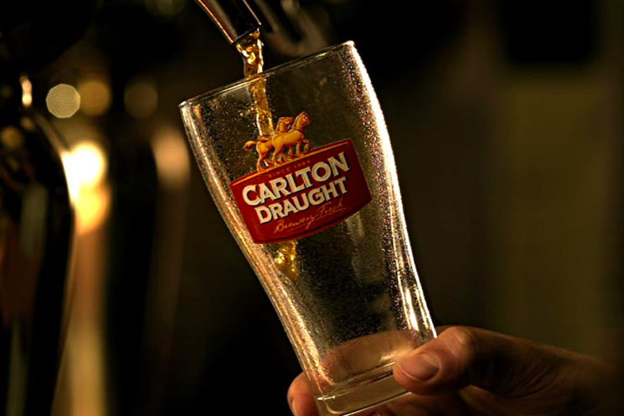 Beer being poured into a Carlton Draught glass