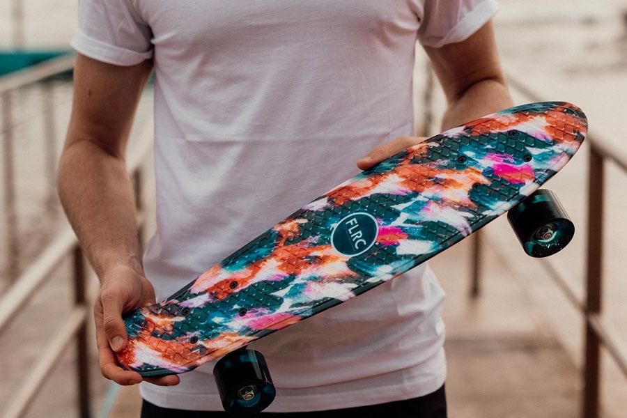 A man holding Flatrock skateboard in front