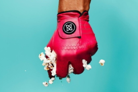 A hand wearing G/FORE collection golf glove squeezing popcorn in fist