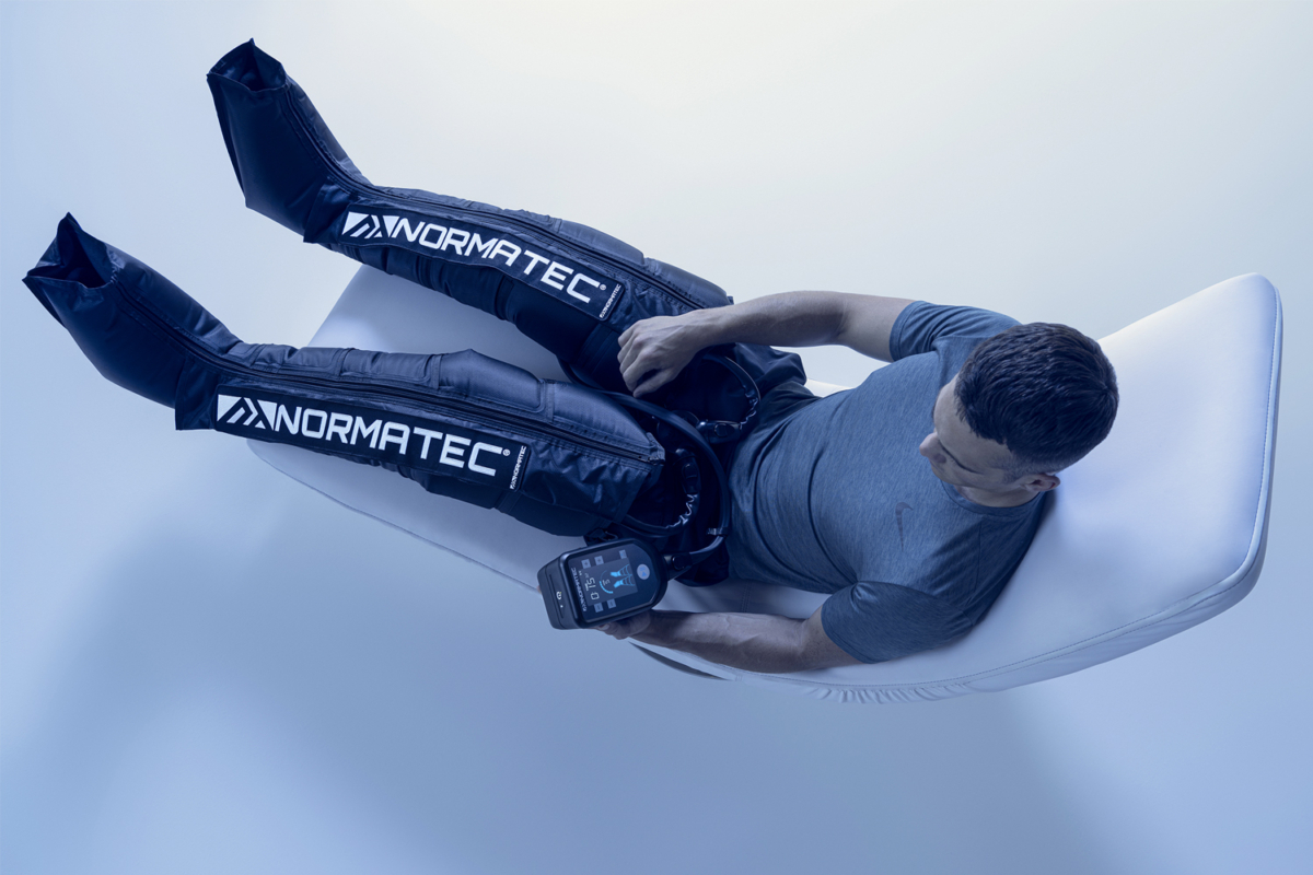 Top view of a man wearing Hyperice Normatec 2.0 Leg System resting on a recliner