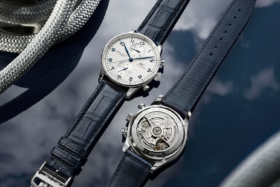 Two IWC Portugiesers on table. One with dial on top and one with caseback on top