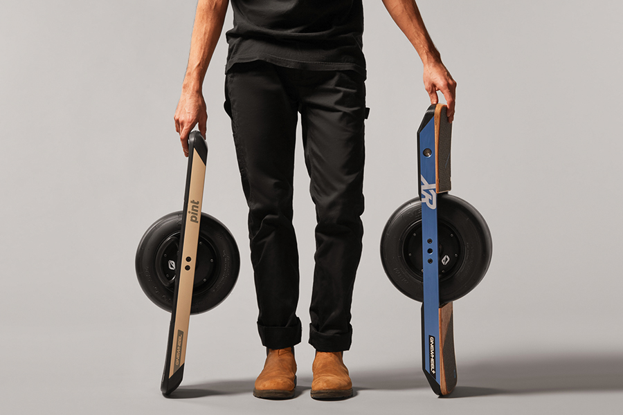 A standing man holding two Onewheels on either sides