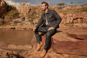 A man sitting on a rock inR.M. Williams new Summer Collection clothes