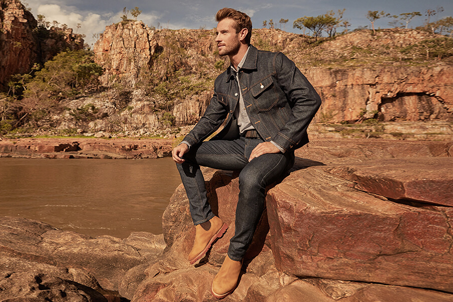 A man sitting on a rock in R.M. Williams new Summer Collection clothes