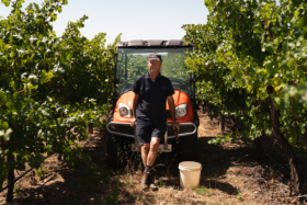 Jock Harvey in middle of vineyard leaning his back on the front hood of a small farm car