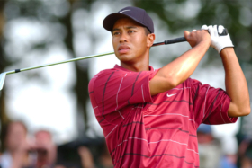 Tiger woods looking at a golf ball after a hit