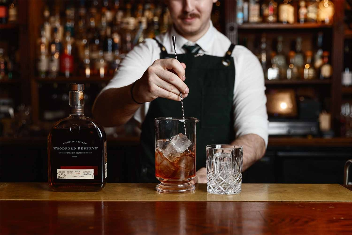 A bartender making a whiskey drink with ice cubes in a glass
