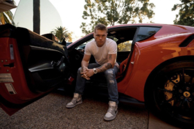 """Cinnamon"" Alvarez sitting in a Lamborghini seat with his feet outside"