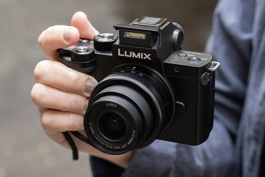 A hand holding a Panasonic Lumix G100 camera
