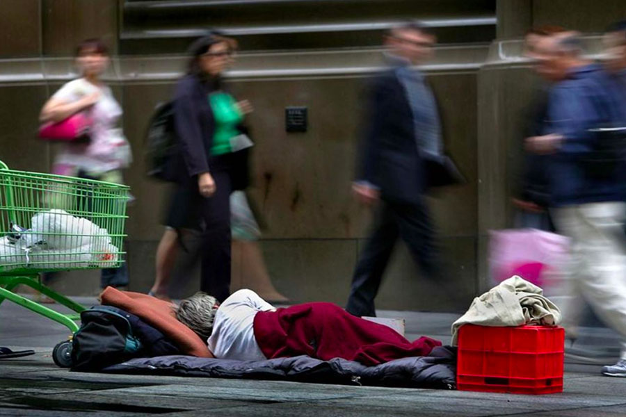 A homeless person sleeping on pavement as people walk by
