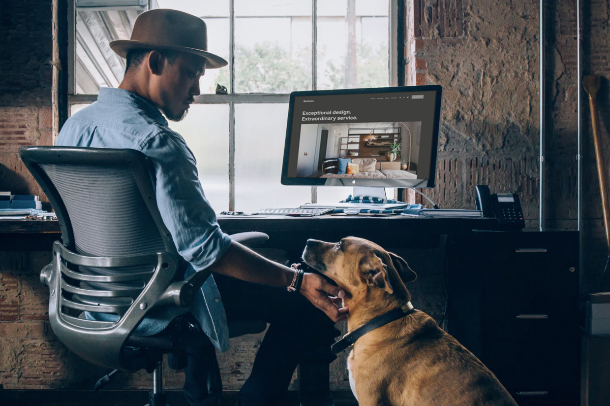 A man rubbing his dog's neck from his chair