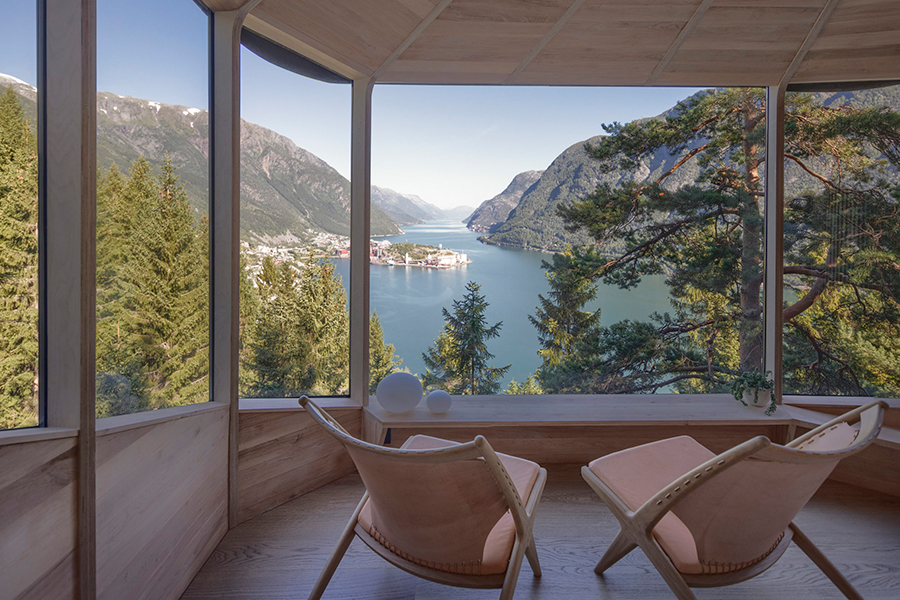 Woodnest Cabin with chair overlooking the glass window